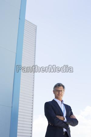 businessman standing below highrise buildings