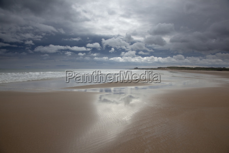clouds reflected in water on beach