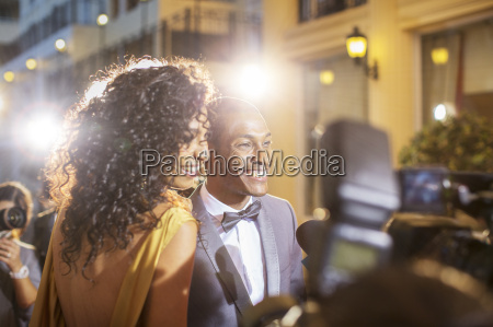 smiling celebrity couple being interviewed and
