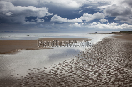clouds over beach at low tide