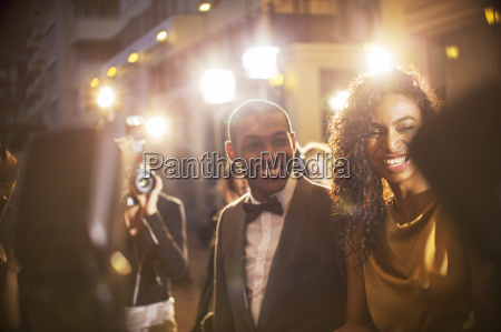 smiling celebrity couple being photographed by