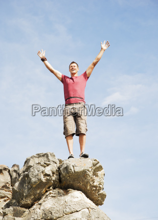 climber cheering on rocky hilltop