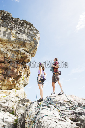 climbers examining steep rock face