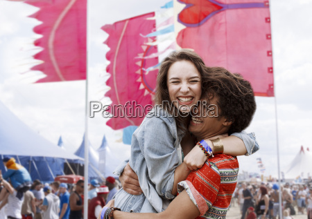 enthusiastic couple hugging at music festival