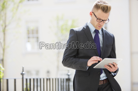 businessman using digital tablet on city