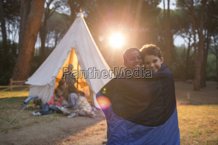 boys wrapped in blanket at campsite