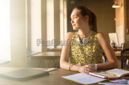 pensive casual businesswoman with headphones looking