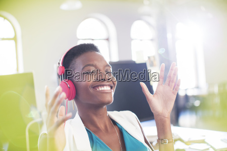 smiling businesswoman listening to music on