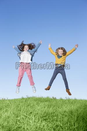 girls jumping for joy on grassy
