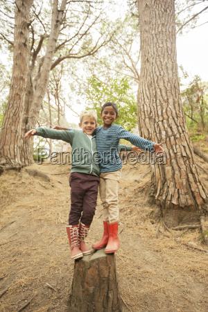 children climbing on stump in forest