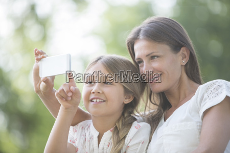 mother and daughter using cell phone