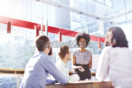 businesswoman leading meeting in sunny office
