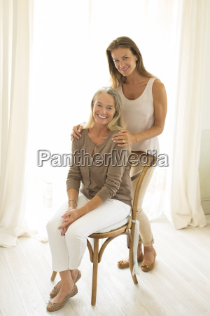 mother and daughter smiling at window