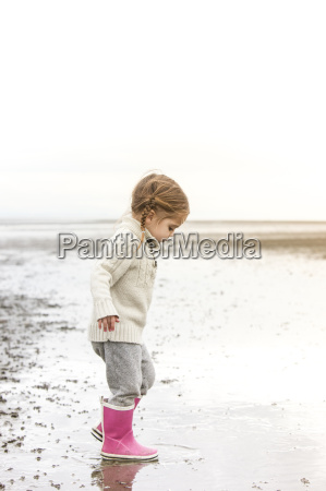 girl in pink rain boots playing