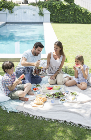family enjoying picnic in backyard