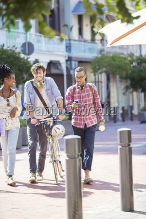 friends walking together on city street