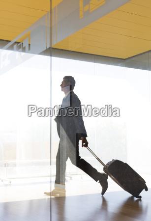 businessman pulling suitcase in airport corridor