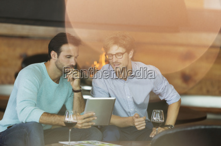 men drinking red wine and using