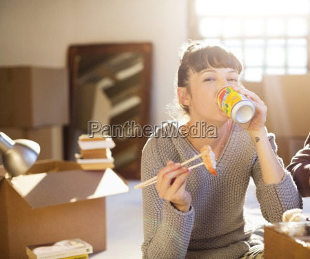 woman drinking soda and eating sushi