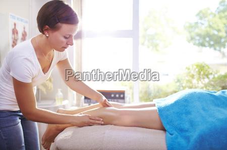 physical therapist massaging womans leg