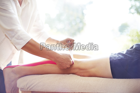 physical therapist applying kinesiology tape to