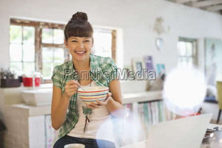 woman eating in kitchen