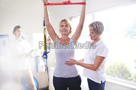 physical therapist guiding woman pulling resistance