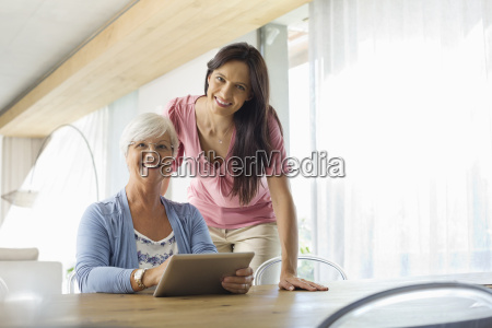 women using tablet computer at table