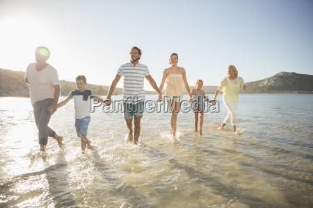 family walking in shallow water on