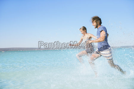 couple running in water on beach