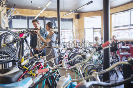 couple browsing bicycles on rack in