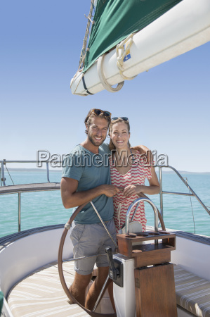 couple steering sailboat together