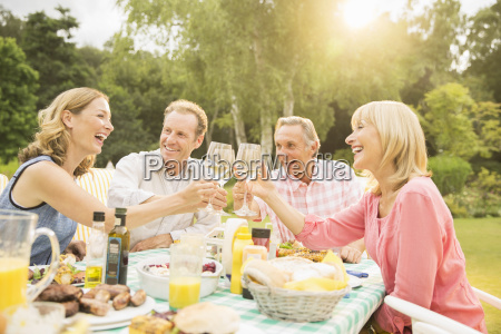 couples toasting wine glasses at table