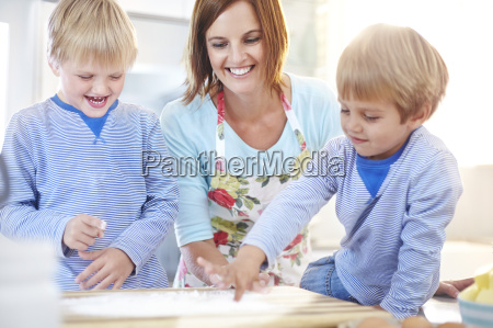 mother and sons baking in kitchen