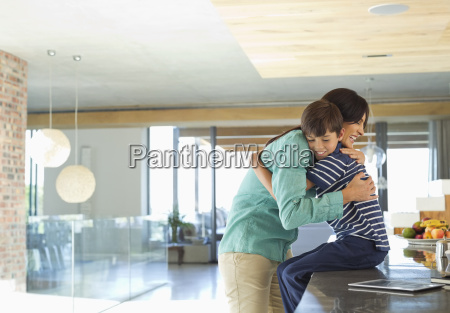 mother hugging son in kitchen