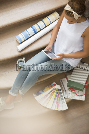 woman using digital tablet on stairs