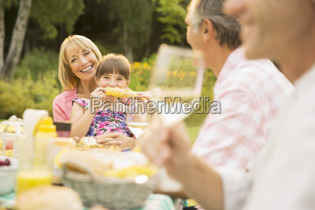 family eating at table in backyard