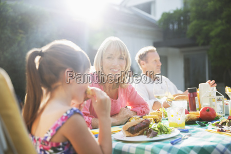family eating lunch at patio table