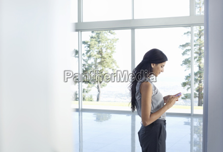 businesswoman using cell phone at window
