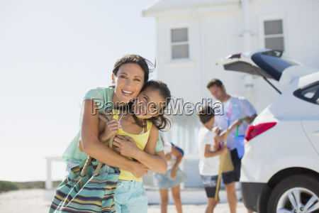 mother and daughter hugging outside beach