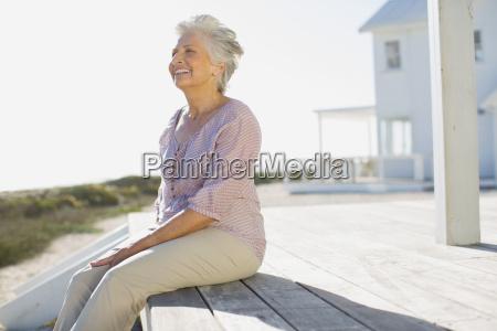 senior woman sitting on deck outside