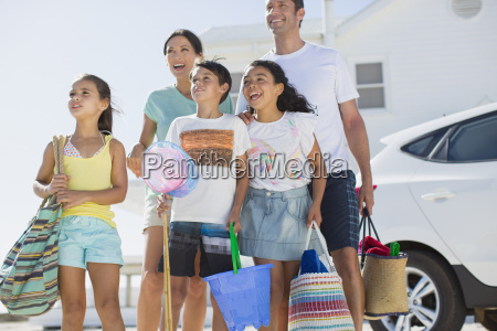 family standing with beach gear in