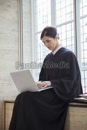 judge sitting on bench using laptop