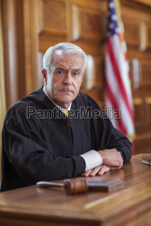 judge sitting at judges bench in