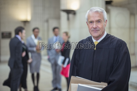 judge holding legal documents in courthouse