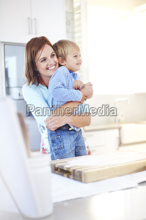 smiling mother hugging son in kitchen