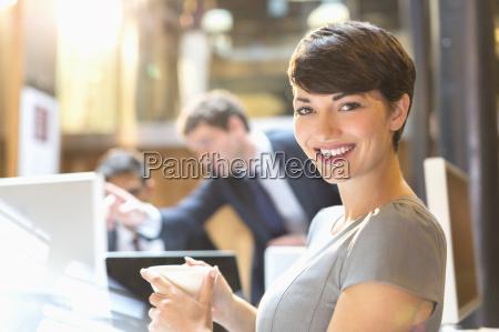 portrait confident businesswoman drinking coffee in