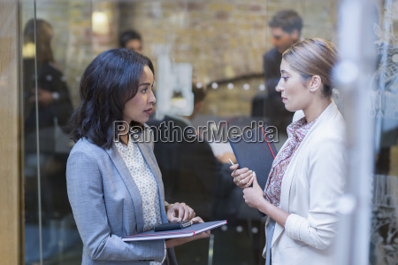 businesswomen talking outside conference room meeting