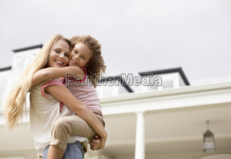 mother and daughter hugging outside house