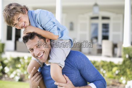 father and son playing outside house